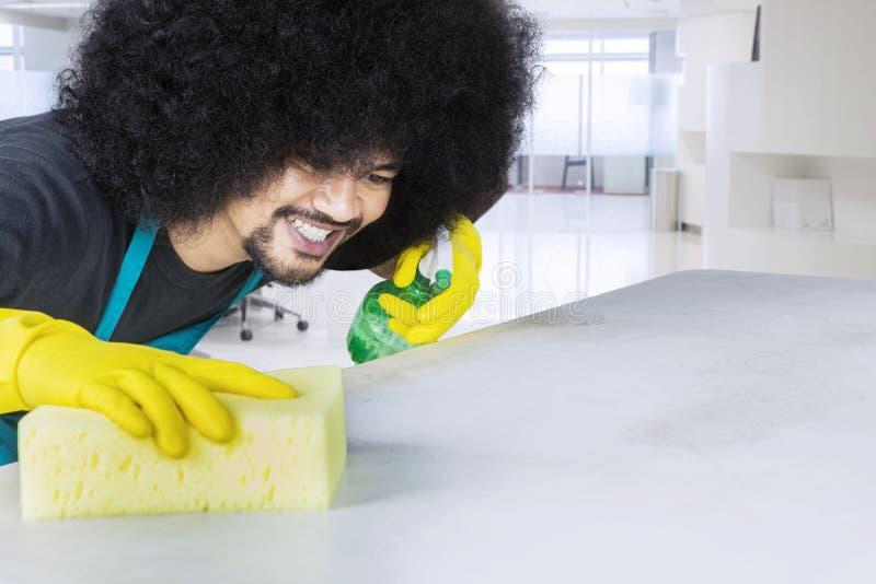Молодой профессионал уборки очищая стол стоковое изображение
