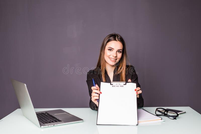 Молодой пункт бизнес-леди для того чтобы прикрыть доску сзажимом для бумаги в офисе стоковые фотографии rf