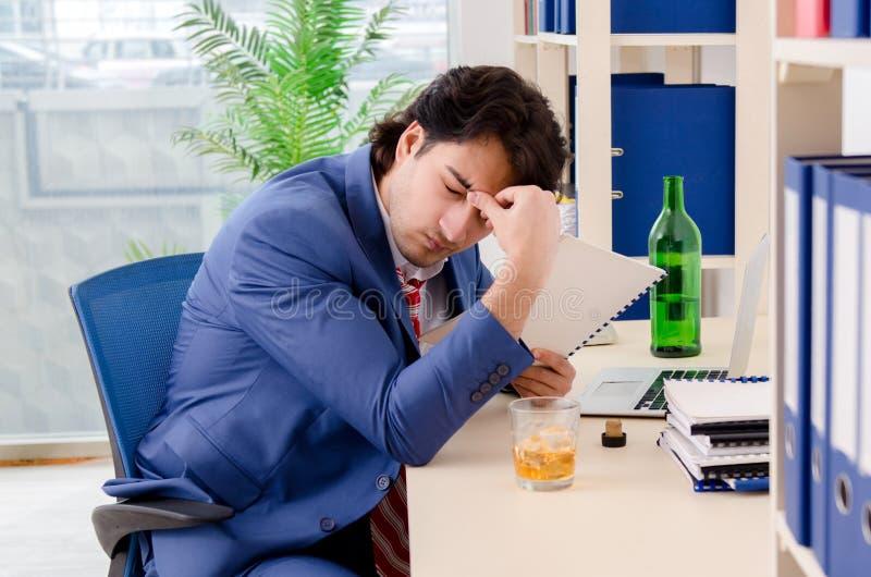 Молодой работник бизнесмена выпивая в офисе стоковые фотографии rf