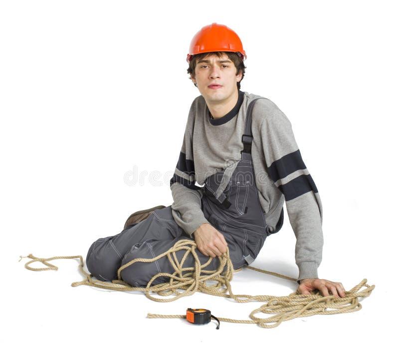 Молодой работник в серой форме связанной вверх с веревочкой на белизне изолировал предпосылку стоковое изображение rf