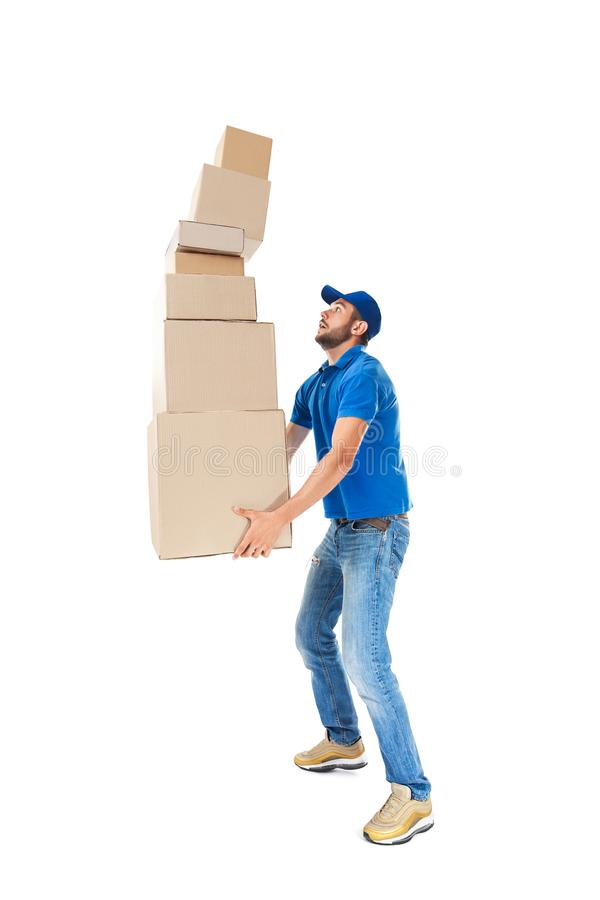 Молодой работник доставляющий покупки на дом с падая стогом коробок стоковое фото rf
