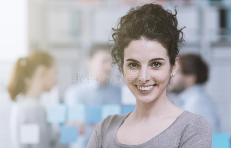 Молодой работник офиса усмехаясь и представляя стоковые фото