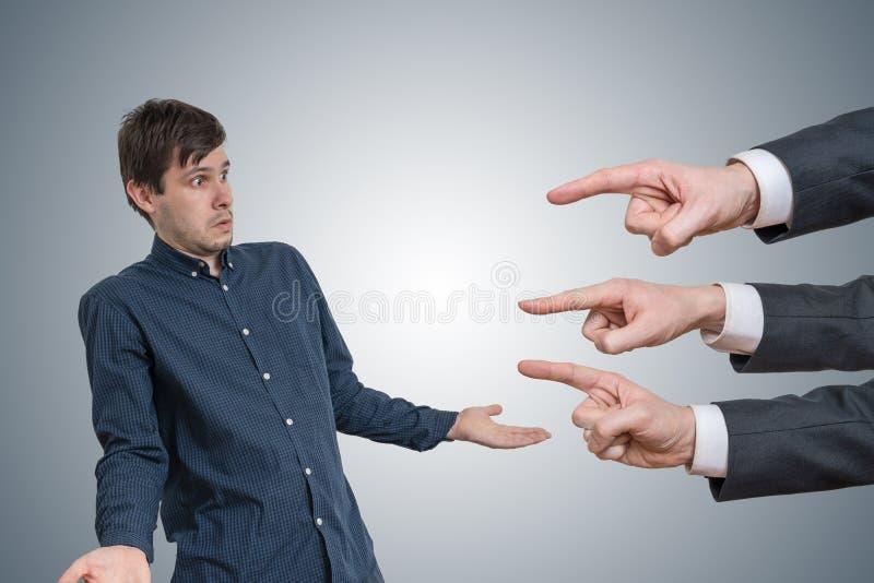 Молодой работник получает увольнятьым Много рук обвиняют его стоковое фото rf