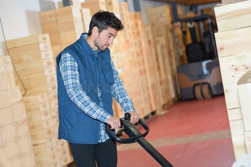 Молодой работник склада используя pallettruck для того чтобы схватить паллет стоковое изображение rf