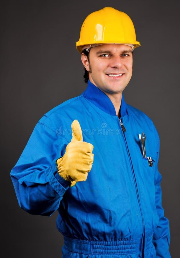 Молодой рабочий-строитель давая большой палец руки вверх по знаку стоковое изображение rf
