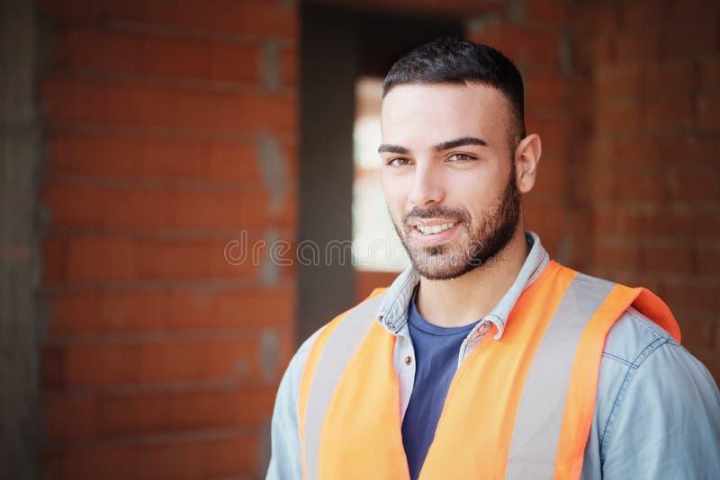 Молодой рабочий-строитель усмехаясь на камере в новом здании стоковое фото rf