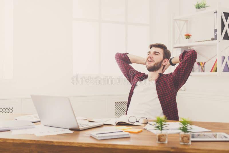 Молодой расслабленный бизнесмен с компьтер-книжкой в современном белом офисе стоковая фотография