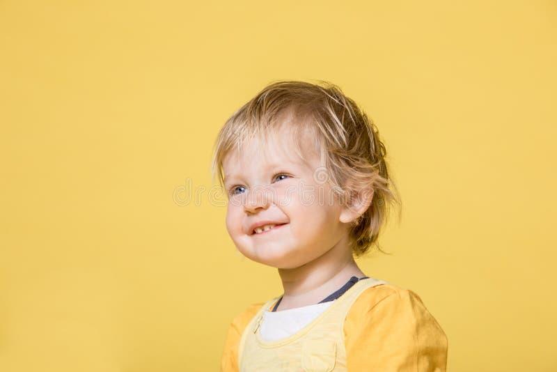 Молодой ребенок в желтом платье на желтой предпосылке стоковые фотографии rf