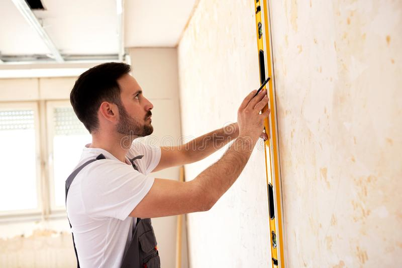 Молодой ремонтник проверяя выровняна ли поверхность стоковое изображение