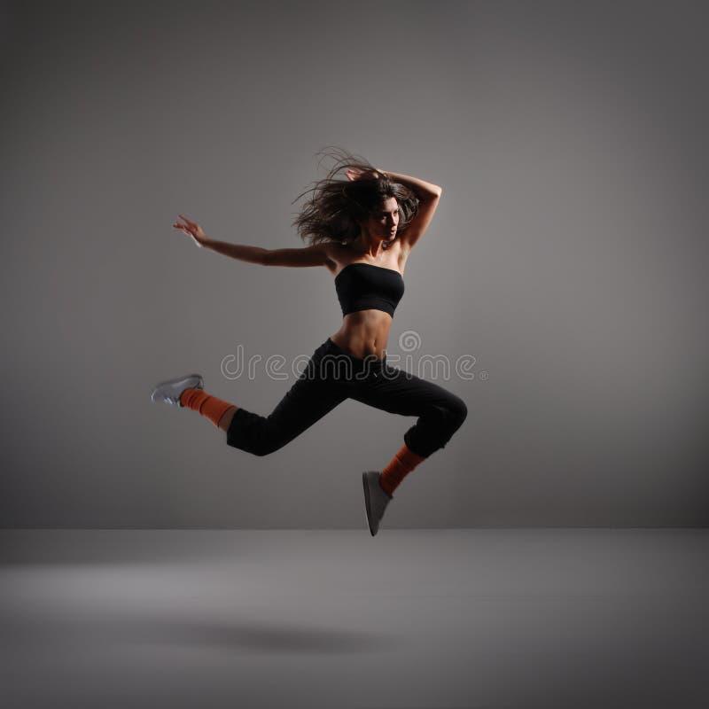 Молодой самомоднейший танцор над серой предпосылкой стоковое изображение rf