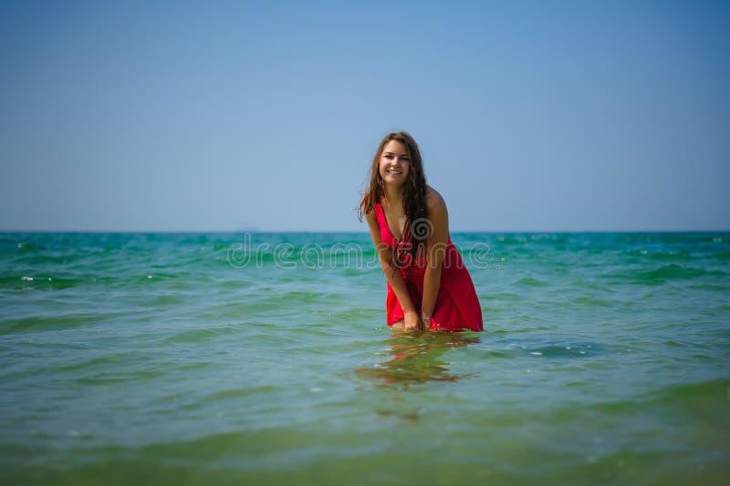 Молодой сексуальный длинн-с волосами брюнет в красном платье пляжа стоит в воде бирюзы океана на горячий день r стоковые изображения