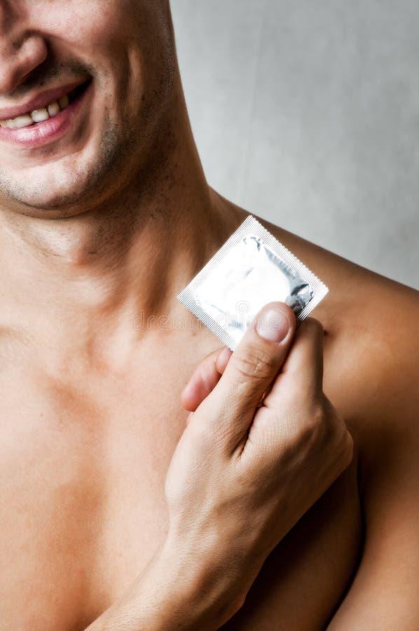 Молодой сексуальный сь презерватив удерживания человека стоковое изображение rf