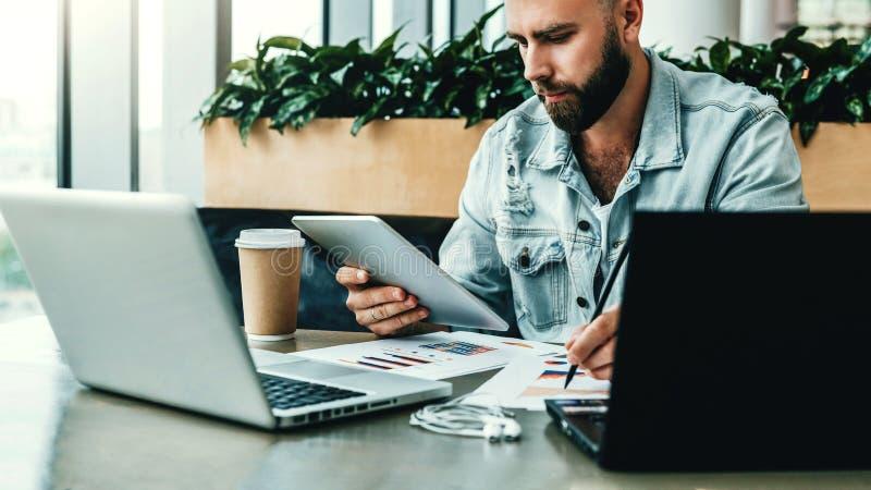 Молодой серьезный бизнесмен сидит в офисе перед компьтер-книжками, используя цифровую таблетку, делая примечания на диаграмме стоковая фотография rf