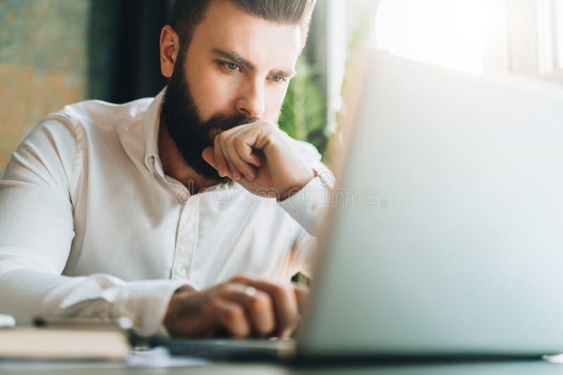 Молодой серьезный бородатый бизнесмен сидя в офисе на таблице и используя компьтер-книжку Человек работает на компьютере, проверя стоковая фотография