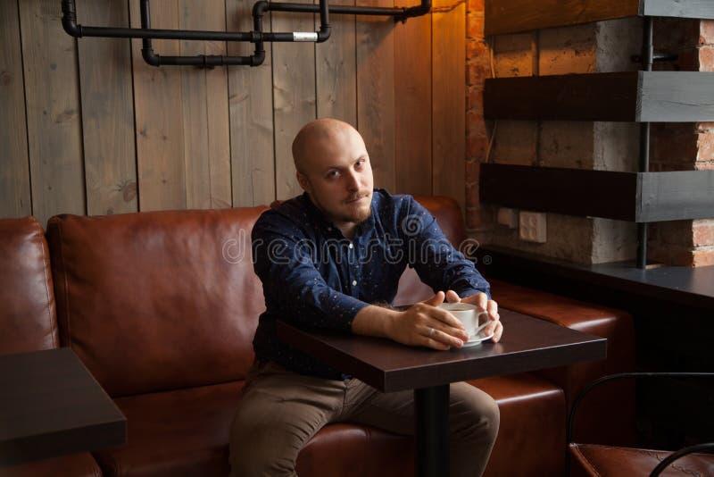 Молодой серьезный модный человек сидя самостоятельно в просторная квартира-введенном в моду кафе стоковое изображение