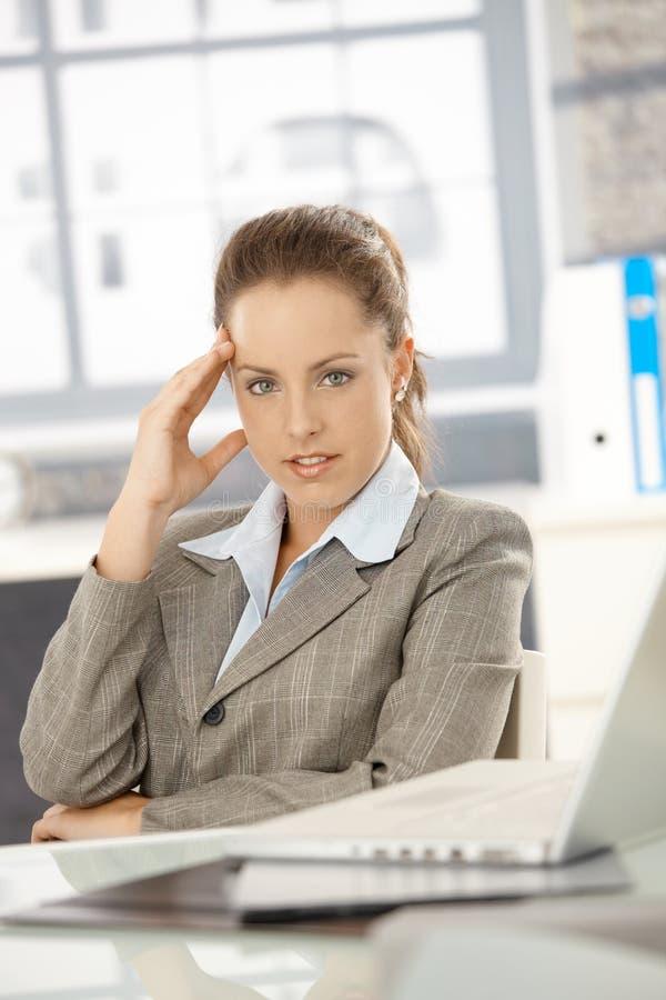 Молодой сидеть коммерсантки утомлял в офисе стоковые изображения