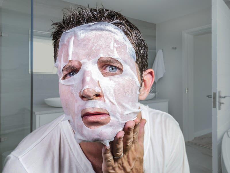 Молодой смешной и грязный человек прикладывая маску красоты лицевую смотря к зеркалу удивленному и страшить в концепции вызревани стоковое изображение