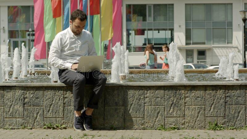 Молодой современный фрилансер бизнесмена работая на его компьютере пока сидящ около фонтана стоковые фото