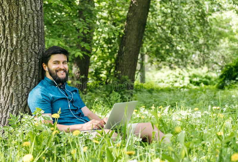 Молодой современный фрилансер бизнесмена работая на компьютере и sitt стоковая фотография