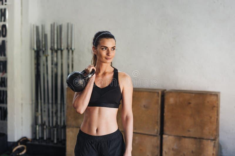 Молодой спортсмен в sportswear делая разминку с kettlebell стоковая фотография rf