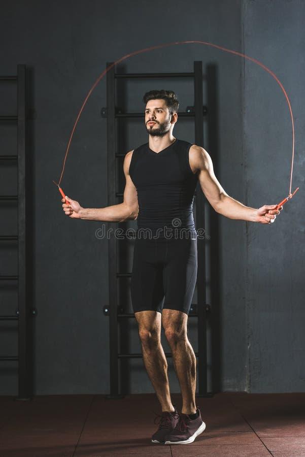 Молодой спортсмен делая разминку веревочки скачки стоковая фотография