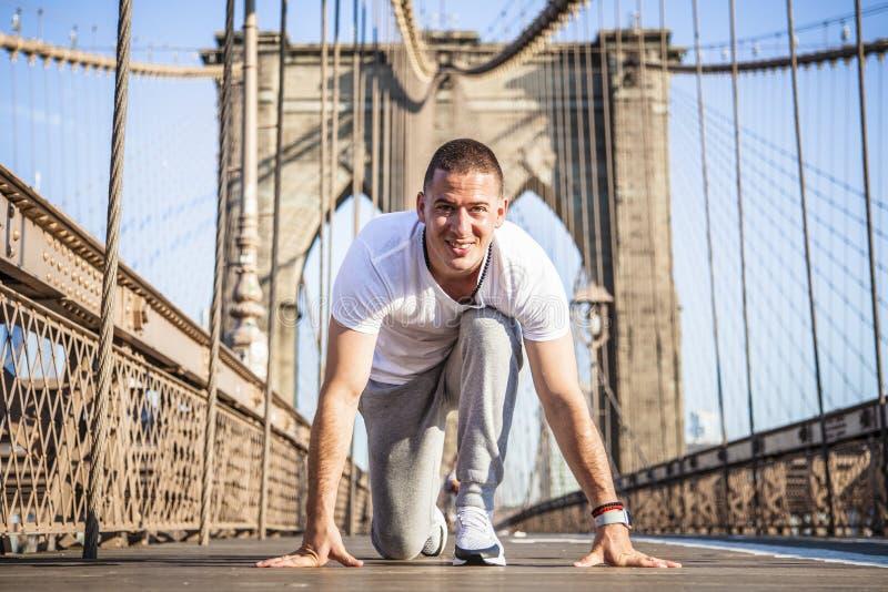 Молодой спринтер спортсмена подготавливая начать гонку на Бруклинском мосте стоковая фотография