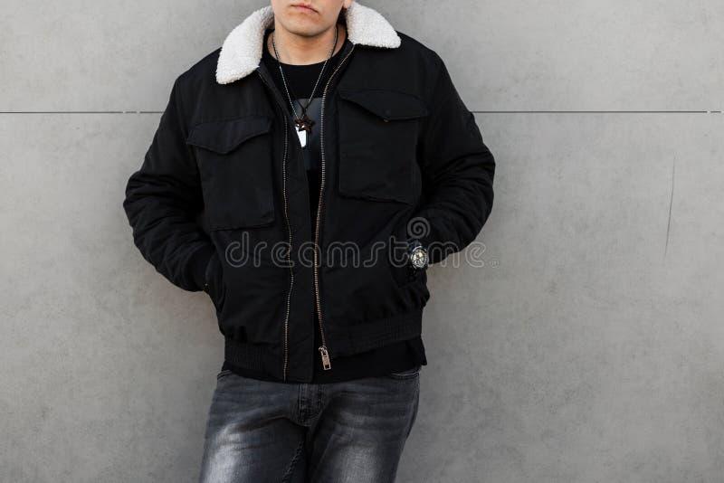 Молодой стильный человек в черной ультрамодной куртке с белым воротником в винтажных серых джинсах в черной футболке стоит около  стоковые изображения rf
