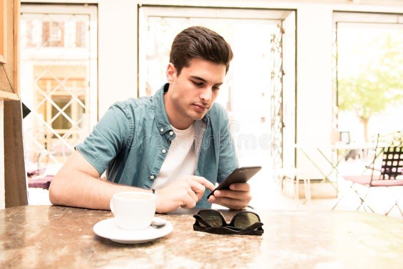 Молодой студент используя его умный телефон для того чтобы прочитать текст пока имеющ кофе стоковая фотография