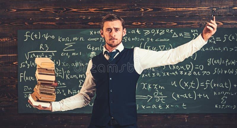 Молодой студент с его руками распространенными как масштабы с кучей книг в одной руке и телефоне в других самомоднейше стоковое фото rf