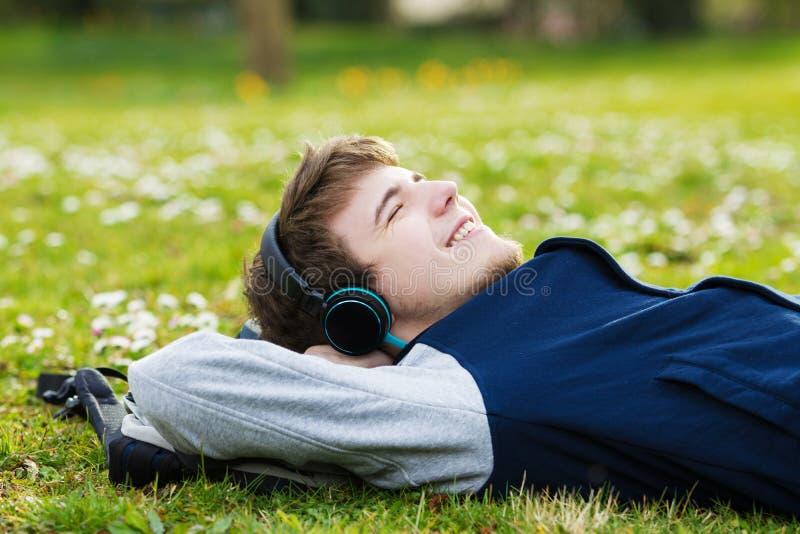 Молодой студент, укомплектовывает личным составом ослабляя усмехаться пока лежащ на траве и lis стоковые фото