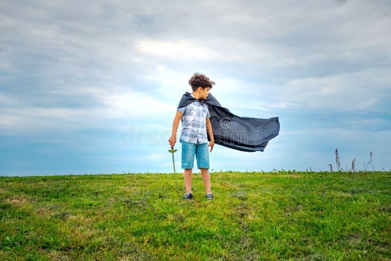 Молодой супергерой мальчика с дуя плащем стоковое фото