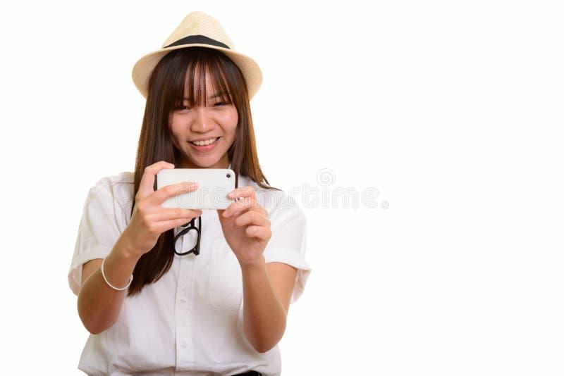 Молодой счастливый азиатский девочка-подросток усмехаясь и фотографируя с m стоковые фото