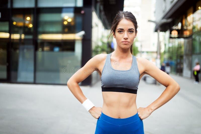 Молодой счастливый бегун женщины jogging в городе на открытом воздухе стоковое изображение