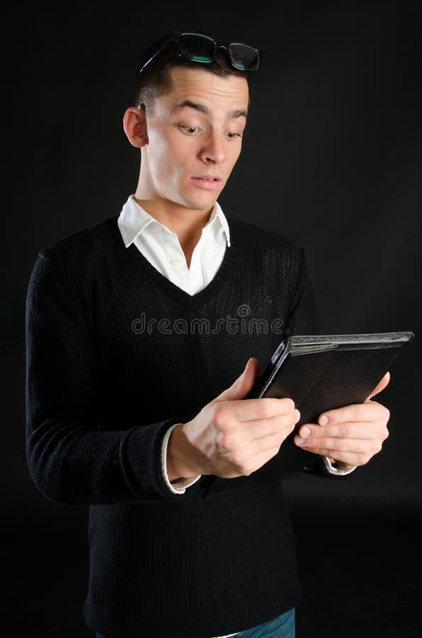 Молодой счастливый бизнесмен держа таблетку стоковое изображение