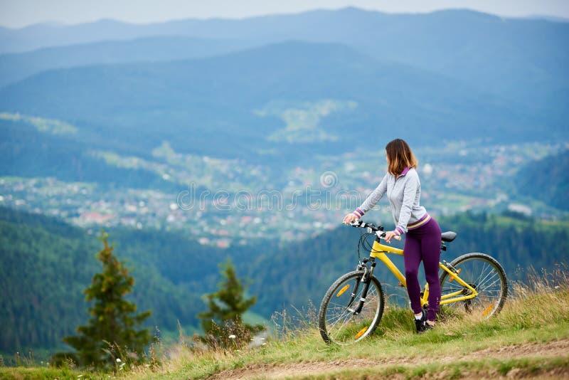 Молодой счастливый велосипед катания женщины в горах на летнем дне стоковое изображение