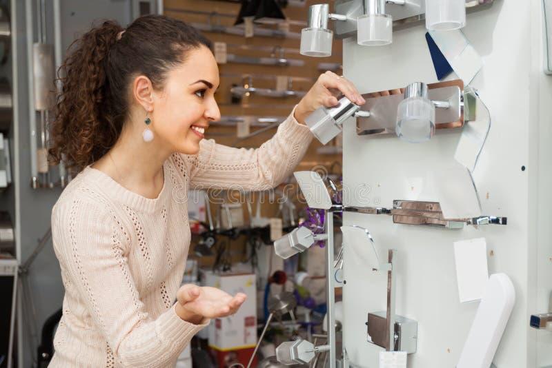 Молодой счастливый женский клиент покупая внутренние света для дома стоковое изображение rf