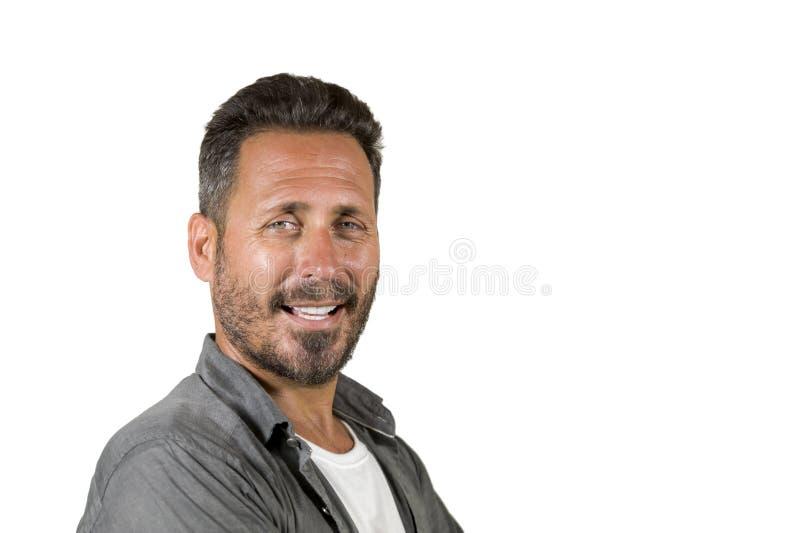 Молодой счастливый и красивый человек 40s с голубыми глазами и борода в случайной рубашке представляя в крутой усмехаться ориента стоковое фото rf