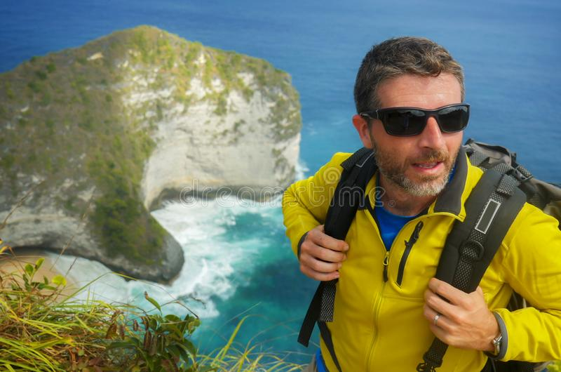 Молодой счастливый и привлекательный sporty человек hiker с trekking рюкзаком на море перемещение чувства ландшафта скалы свободн стоковая фотография