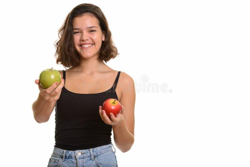 Молодой счастливый кавказский девочка-подросток усмехаясь держащ красное яблоко и стоковые изображения