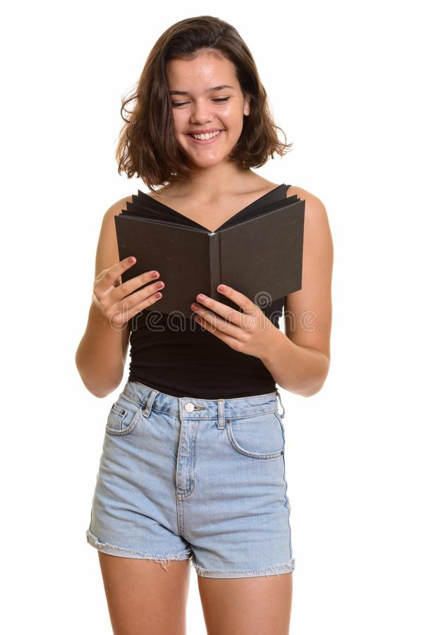 Молодой счастливый кавказский девочка-подросток усмехаясь и книга чтения стоковые изображения rf