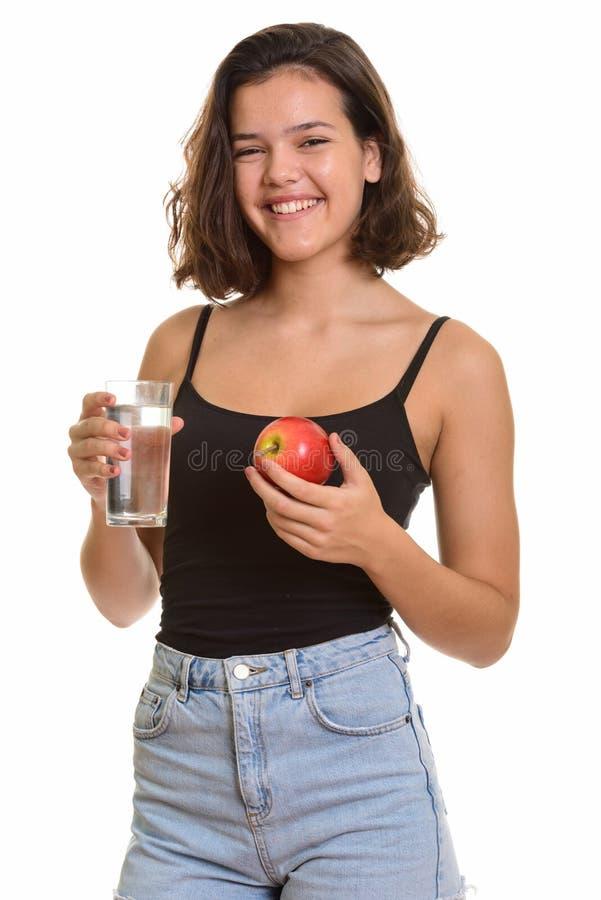 Молодой счастливый кавказский девочка-подросток усмехаясь пока держащ стеклянный o стоковые изображения rf