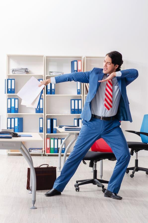 Молодой счастливый мужской работник в офисе стоковые изображения rf