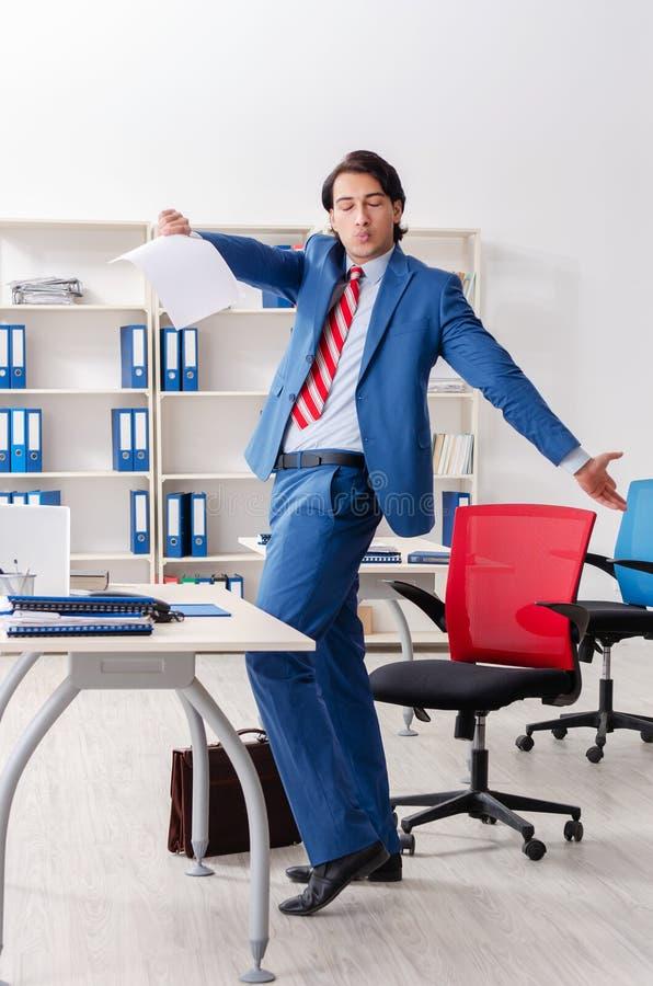 Молодой счастливый мужской работник в офисе стоковое изображение