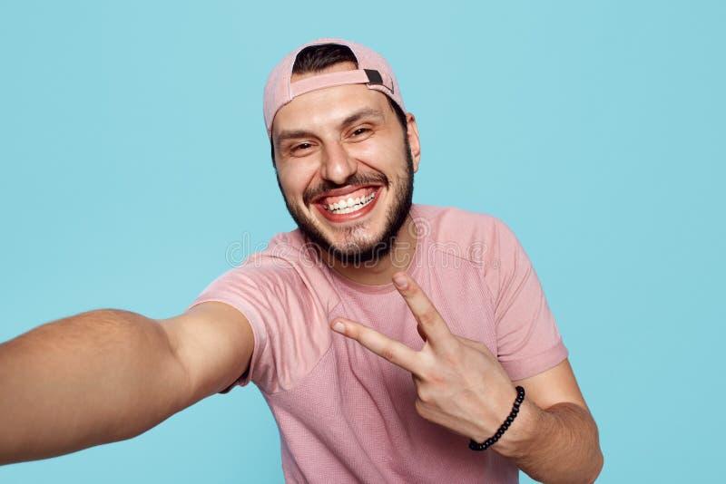 Молодой счастливый мужчина нося розовую футболку и крышку делая selfie и  стоковая фотография rf