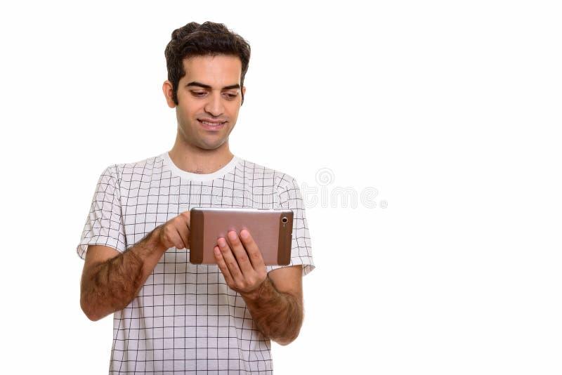 Молодой счастливый персидский человек используя цифровой планшет стоковое изображение rf