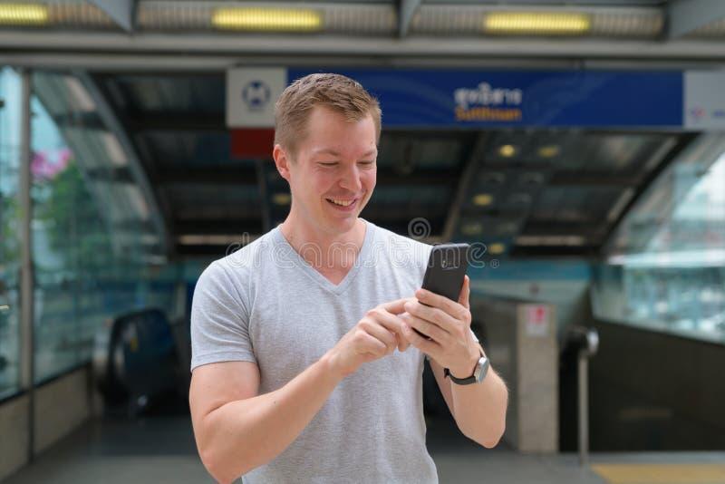 Молодой счастливый туристский человек используя телефон во фронте вокзал в Бангкоке стоковое фото rf