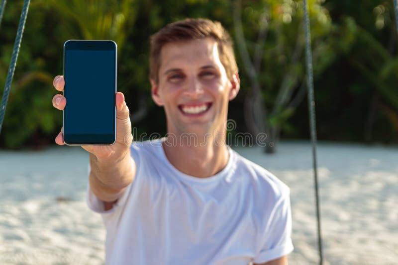 Молодой счастливый человек усаженный на качание показывая вертикальный экран телефона Белые песок и джунгли как предпосылка стоковое фото rf