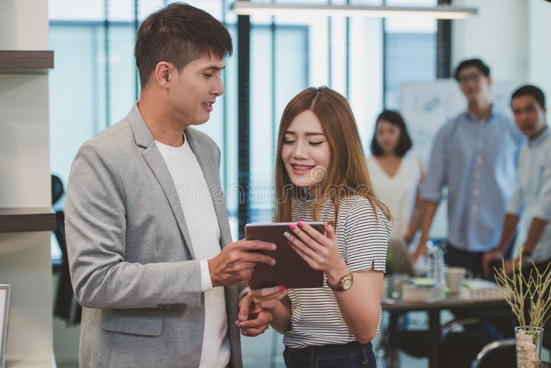 Молодой творческий бизнесмен держа цифровую таблетку с женским co стоковое фото