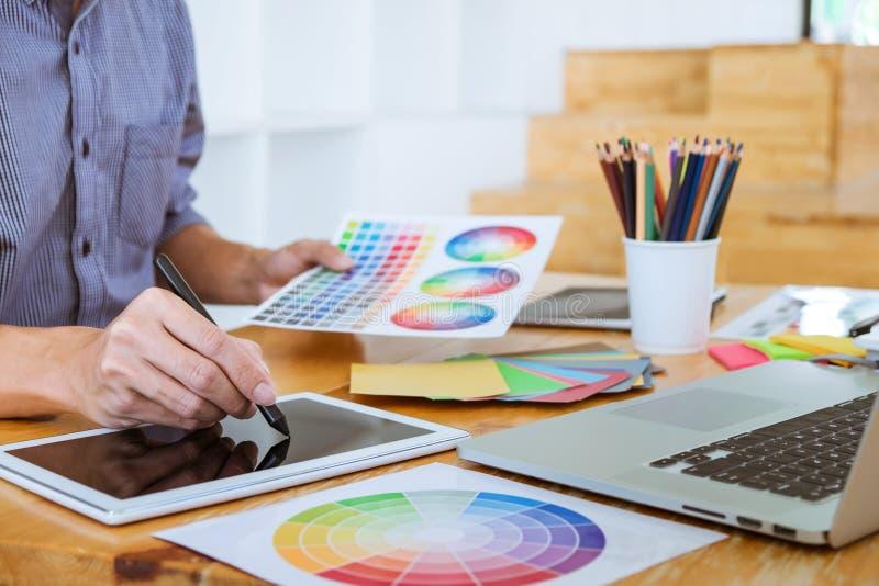 Молодой творческий график-дизайнер работая на образцах чертежа и цвета проекта архитектурноакустических, расцветке выбора на граф стоковое фото rf
