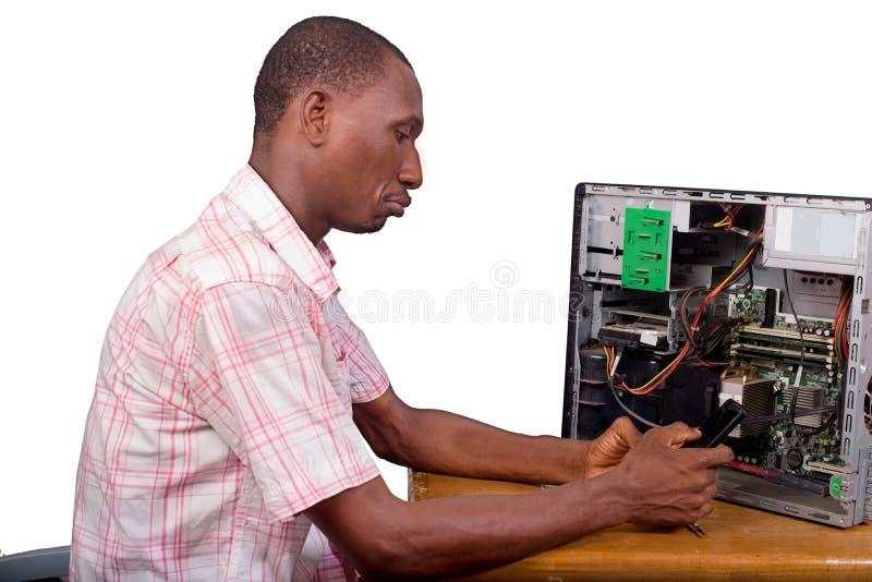Молодой техник сидя и ремонтируя настольный компьютер внутри для стоковое фото rf